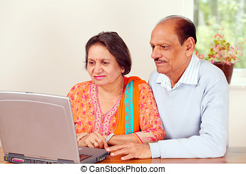 Mature indian couple on computer - Mature indian couple on...