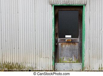 Old wood door on corrugated wall