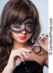 Closeup portrait of attractive young brunette girl with long dark ringlets and fine art manicure wearing lacy mask on her eyes holding graceful silver mouthpiece with thin ladies' cigaret on blue bac