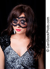 portrait of attractive young brunette girl with long dark ringlets and lacy mask on her eyes on black background