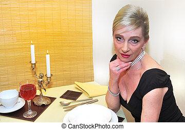 Elegant senior woman waiting for dinner