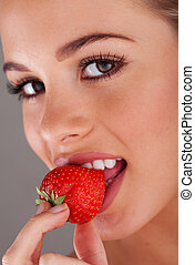 strawberry - Happy young woman eating mellow strawberry