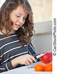 Teen girl with apple - Cute teen girl cutting in the kitchen...