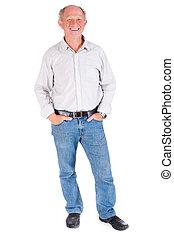 Studio portrait of smiling senior man in casuals against...