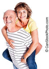 Senior man giving woman piggyback ride, indoors