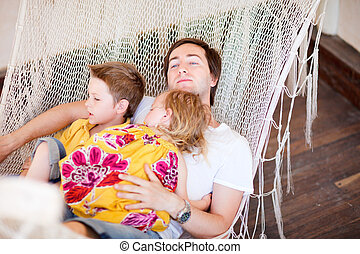 Father and his kids relaxing in hammock - Young father and...