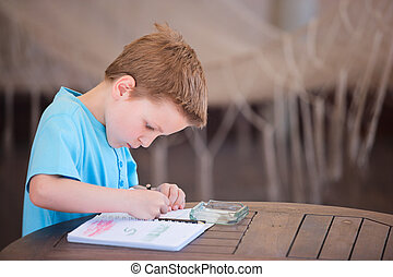 Boy drawing or writing - Little boy drawing or writing at...