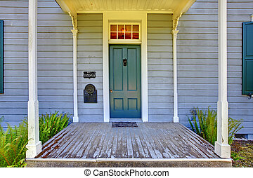 Grey historical house front entrance with green door. -...
