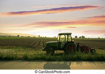 Plowed land and tractor on sunset