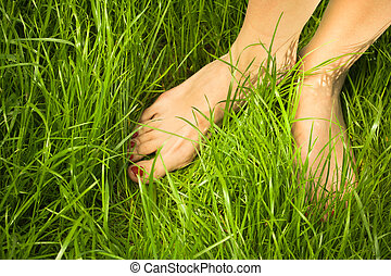 Womans bare feet in green