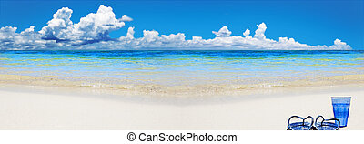 Tropical beach with beach shoes and glass of water