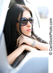 Beautiful attractive woman in car, looking through the window