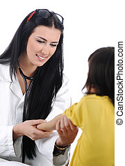 Young female doctor examining little cute child at modern hospital