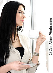 Young pretty woman drinking coffee in office, beside the glass window