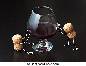 Figures from wine corks and a glass of wine