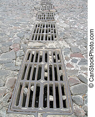 sewerage on stone road, metallic - many metallic mesh on...