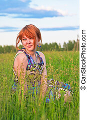 Beautiful ginger-haired woman sitting on the ground at meadow