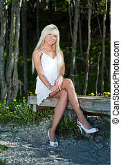 girl sitting on a bench in the woods - girl in white dress...