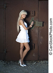 girl opens old garage - girl in white dress opens old garage...