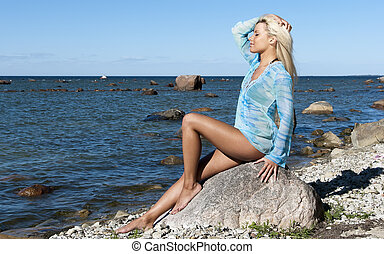 girl in a blue tunic is enjoying summer on the beach,...