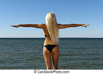 girl in a bikini turned her back and looks at the blue sea -...