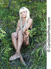 blonde girl in a black bathing suit sitting in the forest -...