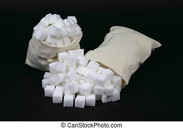 Spilled Cubes Sugar from bags over black.