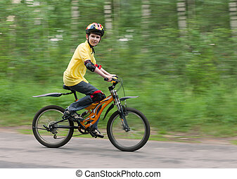 the boy on a bike - The boy goes on a bicycle. Shallow DOF,...