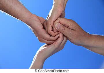 Hands - Various peoples hands in front of bright blue sky