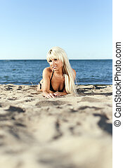 blonde girl in a black bathing suit lying on the shore of...