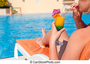 Woman hand drinking cocktail near swimming pool - Woman hand...