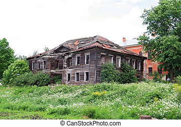 old wooden house on green field