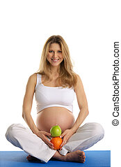Pregnant woman practicing yoga and keeps fruit isolated on...