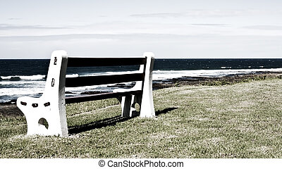 Bench on grass next to the ocean in grunge infrared effect