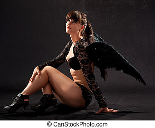 girl in black underwear and black wings on a black...