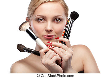 Young woman with make up brushes isolated on white