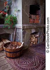 cosy veranda with fireplace, firewood and barrel full of...