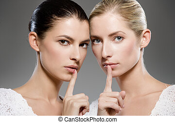 women's secrets - two young caucasian women gesturing shh -...