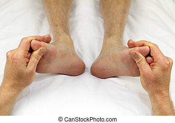 Foot Reflexology - Big toes of both feet of an adult male...