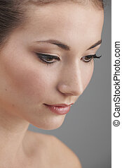 Make-Up - Young womans face with subtle make up and eye lash...