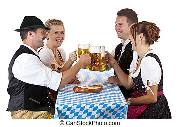 Bavarian men and women toast with Oktoberfest beer stein...