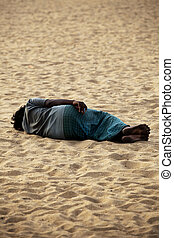 Homeless man sleeping in beach