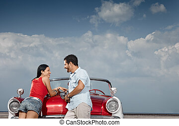 man and beautiful woman leaning on cabriolet car - hispanic...