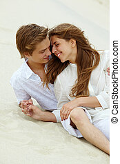 Relaxing dates - Photo of happy couple relaxing on sand...