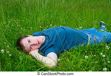 The young man lies on a green meadow