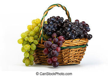 Clusters of yellow and black grapes in a basket on a white...