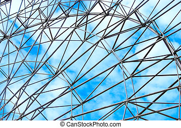 detail of a ferris wheel in front of blue sky