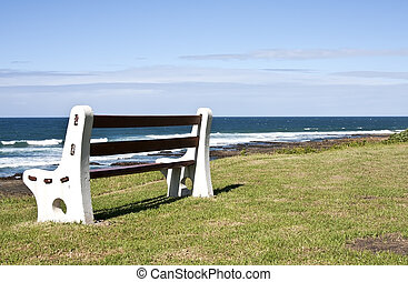 Bench on grass next to the ocean in sunshine