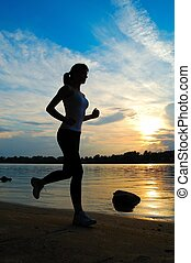 Silhouette of beautiful woman running on sunset