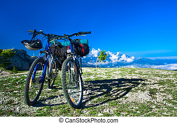 two bikes on the precipice, sky and mountains in the...